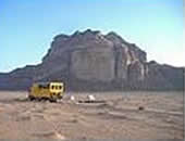 The tour bus crosses an arid desert on an Oasis Overland trip