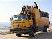 A yellow truck loaded with explorers on Oasis Overland adventures abroad